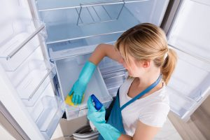 High Angle View Of Young Woman Cleaning Empty Refrigerator